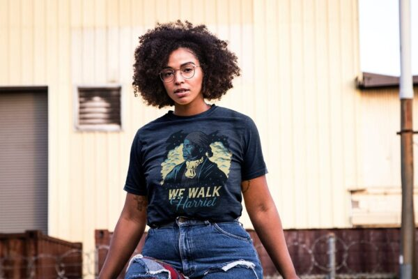 Mockup of a Tattoed Black Woman with Curly Hair Wearing a Plus Size T-shirt in City Outdoors Wearing Glasses B
